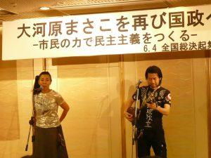 集会のオープニングは、琉球弧の島々で歌い継がれる島唄とオリジナルソングのライブ活動を国内、国外で展開している寿[kotobuki]の二人によるミニライブ。参加者も声をあわせて、にぎやかな開会をなった
