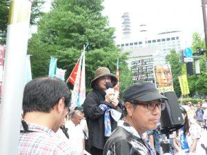 喪をあらわす黒い服装で、主催者あいさつを述べる、沖縄一坪反戦地主会・関東ブロックの外間三枝子さん