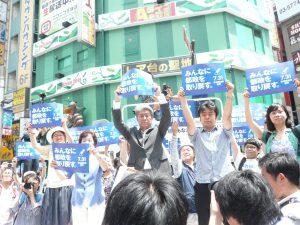 応援に集まったおおぜいの市民とともに、「みんなに都政を取り戻す。」のスローガンパネルを掲げる鳥越俊太郎さん。7月14日